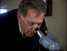 Jack Klugman as Quincy looking in a microscope