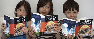 Three kids reading Harry Potter
